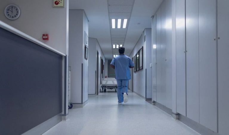 hospital hallway with caregiver walking away
